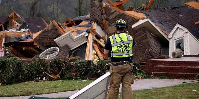 A firefighter surveys damage to a house where the family was trapped, but were able to get out after a tornado touches down south of Birmingham, Ala. in the Eagle Point community damaging multiple homes Thursday, March 25, 2021.