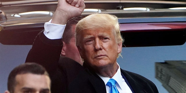 Former U.S. President Donald Trump acknowledges people as he gets in his SUV outside Trump Tower