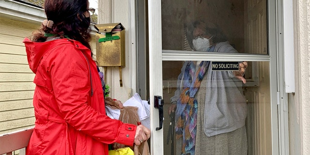 Senior citizen Barbara Bender answers the door for Store to Door employee Nancy Murphy in Portland, Ore., as she delivers an order of groceries for the nonprofit on Feb. 25, 2021. (AP Photo/Gillian Flaccus)