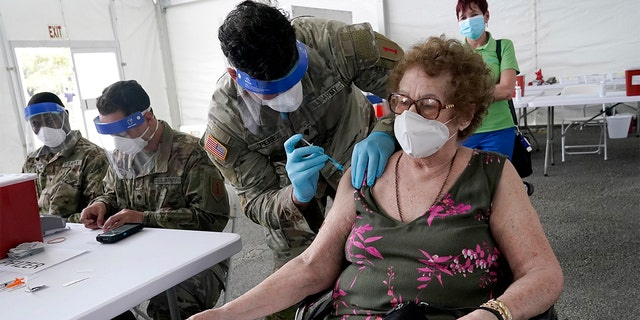 FILE - In this March 3, 2021, file photo, In this Loida Mendez, 86, gets the first dose of the Pfizer COVID-19 vaccine from U.S. Army medic Luis Perez, at a FEMA vaccination site at Miami Dade College in North Miami, Fla. (AP Photo/Marta Lavandier, File)