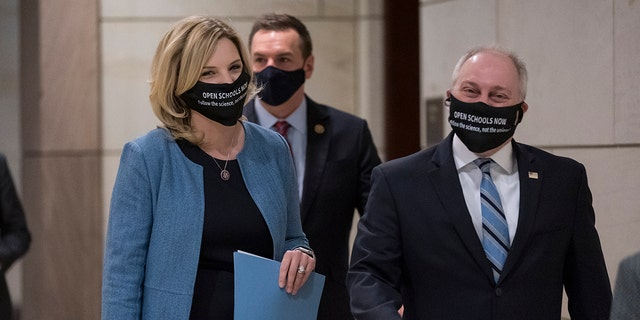Rep. Ashley Hinson, R-Iowa, and Rep. Steve Scalise, R-La., the House minority whip, right arrive to talk to reporters, following a GOP strategy session, at the Capitol in Washington, Tuesday, March 9, 2021.