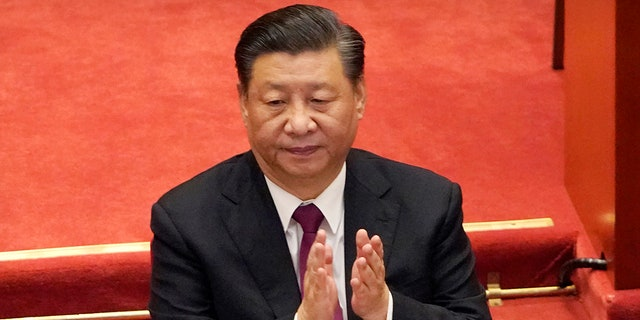 Chinese President Xi Jinping applauds during the closing session of the Chinese People's Political Consultative Conference (CPPCC) at the Great Hall of the People in Beijing, Wednesday, March 10, 2021. Xi's government has overseen genocide and human rights abuses. (AP Photo/Mark Schiefelbein)