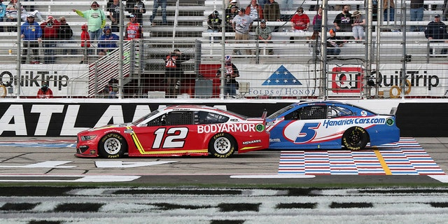 Blaney (12) and Larson (5) cross the start/finish line with eight laps left at Atlanta.
