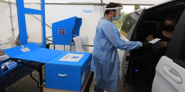 Coronavirus patients cast their ballots Tuesday at a special drive-through polling station in Israel. (Eitan Elhadez/TPS)