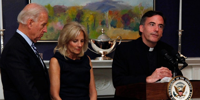 In this Nov. 22, 2010, file photo, Vice President Joe Biden, left, and his wife, Jill Biden, center, stand with heads bowed as the Rev. Kevin O'Brien says the blessing during a Thanksgiving meal for Wounded Warriors in Washington. (AP Photo/Carolyn Kaster, File)