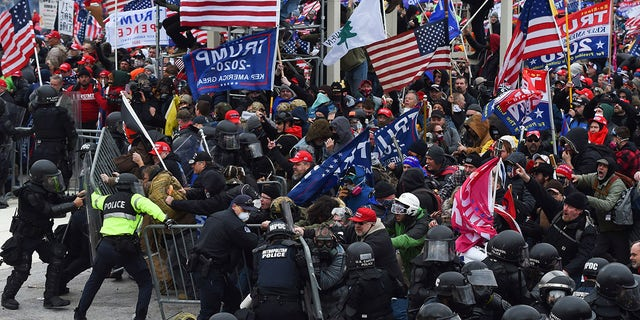 TOPSHOT - Trump supporters clash with police and security forces as they push barricades to storm the US Capitol in Washington D.C on January 6, 2021. - Demonstrators breeched security and entered the Capitol as Congress debated the 2020 presidential election Electoral Vote Certification. (Photo by ROBERTO SCHMIDT / AFP) (Photo by ROBERTO SCHMIDT/AFP via Getty Images)