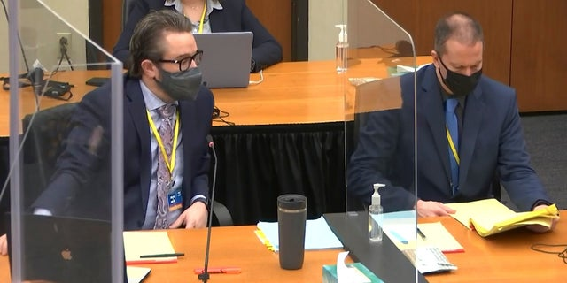 In this image taken from video, defense attorney Eric Nelson, left, and defendant former Minneapolis police officer Derek Chauvin, right, confer before Hennepin County Judge PeterCahill presides over jury selection on Monday. (AP/Court TV)