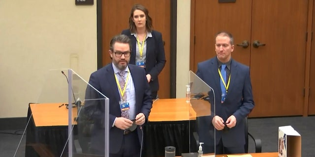 In this image taken from video, defense attorney Eric Nelson, left, defendant former Minneapolis police officer Derek Chauvin, right, and Nelson's assistant Amy Voss, back, introduce themselves to jurors as Hennepin County Judge PeterCahill presides over jury selection in the trial of Chauvin on Monday at the Hennepin County Courthouse in Minneapolis. (AP/Court TV)