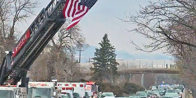Vehicles pass under a giant American flag stationed alongside a road in Boulder, Colo., during a procession for a fallen police officer.