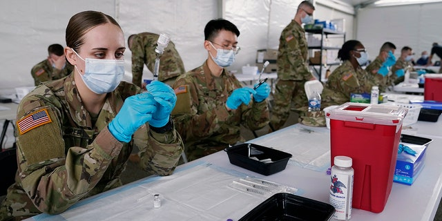 In this March 9, 2021, file photo, Army health specialists fill syringes with the Pfizer COVID-19 vaccine in Miami.