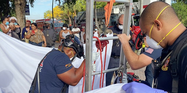 First responders held up a sheet for the victim's privacy as onlookers cheered her rescue.