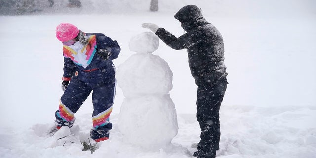 Jimmy Mundell, right, and Abbey Eilermann build a snowman as a snowstorm passed through Denver on Sunday. (AP)