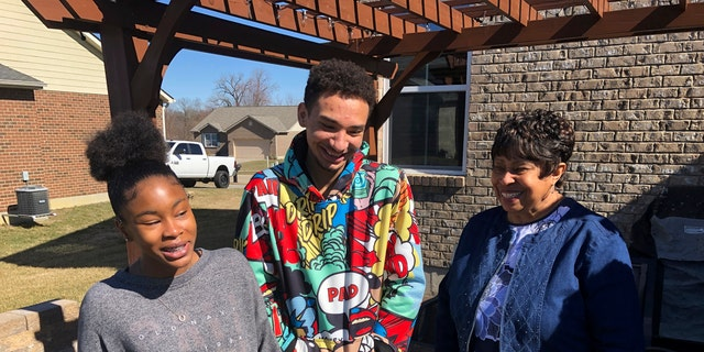 March 7, 2021: Brilee Carter, left,13, and Cobe Calhoun, 17, share a laugh with their great-grandmother, Doris Rolark, outside Rolark's daughter's home in Monroe, Ohio.