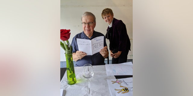 In this Aug, 2020, photo provided by courtesy of Nancy Peters, Joe Peters reads the menu on his birthday in a garage served by grandson, Nate Hoying, right, in Cincinnati.