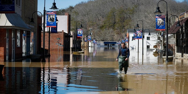 Brad Newnam crosses a flooded East Main Street while checking on businesses in the area in downtown Beattyville, Ky., on Tuesday. Heavy rains caused the Kentucky River to flood most of downtown Beattyville. (AP/Lexington Herald-Leader)