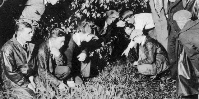 Newsmen and spectators are watching as a young man points to the spot where the body of 19-month-old baby Charles A. Lindbergh Jr., was found in a shallow grave, near Mount Rose, N.J., on May 12, 1932. The infant son of world-famed aviator Charles Lindbergh was kidnapped on March 1, 1932, and found dead, only four-and-a-half miles away from the Lindbergh estate. (AP Photo)
