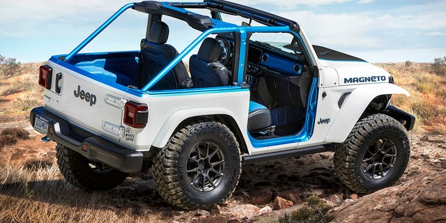 The exterior of the Jeep® Magneto BEV concept features a Bright White color with Surf Blue accents, along with a heavy-duty performance hood with center scoop and custom decal, redesigned rear gate and dramatic full-width forward lighting. Custom Royal Blue and Black leather seats with Sapphire-colored inserts and straps, Surf Blue truck bed liner and Mopar slush mats give the Magneto's interior design an electrified appearance.
