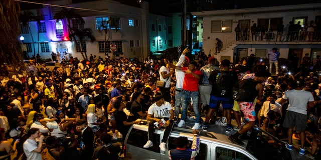 Crowds defiantly gather in the street while a speaker blasts music an hour past curfew in Miami Beach, Fla., on Sunday. An 8 p.m. curfew has been extended in Miami Beach after law enforcement worked to contain unruly crowds of spring break tourists. (AP/Miami Herald)