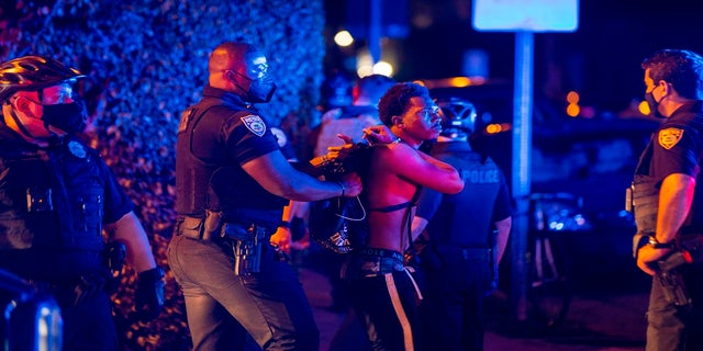 A man is arrested while out a few hours past curfew in Miami Beach, Fla., on Sunday. (AP/Miami Herald)