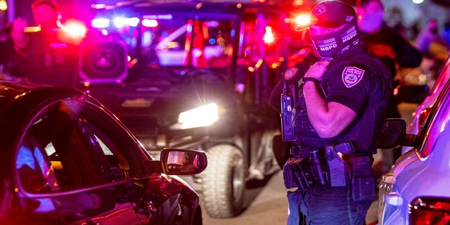 Miami Beach Police arrive on the scene to disperse a crowd that formed near Seventh Street and Alton Road after crowds were sent away from Ocean Drive in Miami Beach, Fla., on Sunday. (AP/Miami Herald)