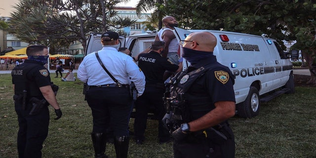An unidentified man is detained and later arrested on Sunday at 5th Street and Ocean Drive in Miami Beach. (AP/Miami Herald)