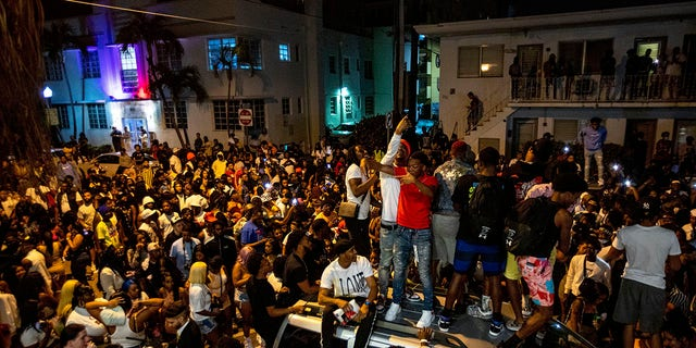 Crowds defiantly gather in the street while a speaker blasts music an hour past curfew in Miami Beach, Fla., on Sunday. (Daniel A. Varela/Miami Herald via AP)