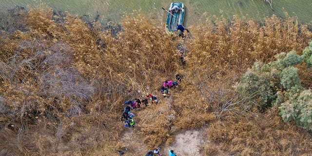 Migrant families and children climb the banks of the Rio Grande River into the United States as smugglers on rafts prepare to return to Mexico in Penitas, Texas, U.S., March 5, 2021.