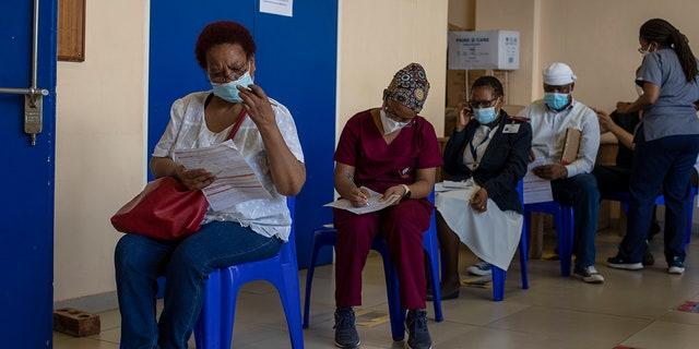 Maggie Sedidi, left, a 59-year-old nurse at Soweto's Chris Hani Baragwanath hospital, reads a medical questioner before receiving her dose of the Johnson & Johnson COVID-19 vaccine at a vaccination center in Soweto, South Africa, Friday, March 5, 2021.