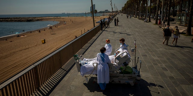 """In this Sept. 4, 2020, file photo, Francisco Espana, 60, is surrounded by members of his medical team as he looks at the Mediterranean sea from a promenade next to the """"Hospital del Mar"""" in Barcelona, Spain."""