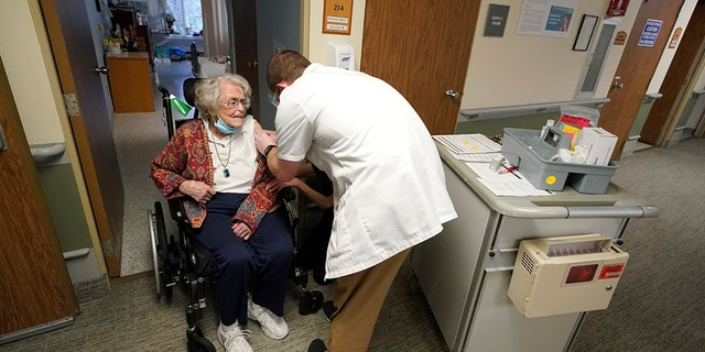 In this Jan. 8, 2021, file photo, Jean Allen, 96, left, receives the first shot of the Pfizer vaccination for COVID-19, from a Walgreens Pharmacist, right, at Queen Anne Healthcare, a skilled nursing and rehabilitation facility in Seattle.