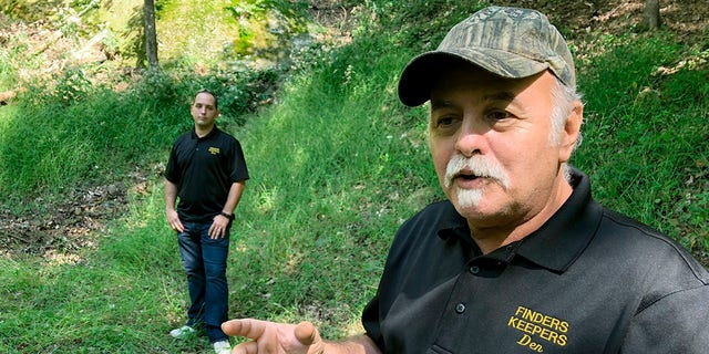 This Sept. 20, 2018 file photo, Dennis Parada, right, and his son Kem Parada stand at the site of the FBI's dig for Civil War-era gold in Dents Run, Pennsylvania. (AP Photo/Michael Rubinkam, File)