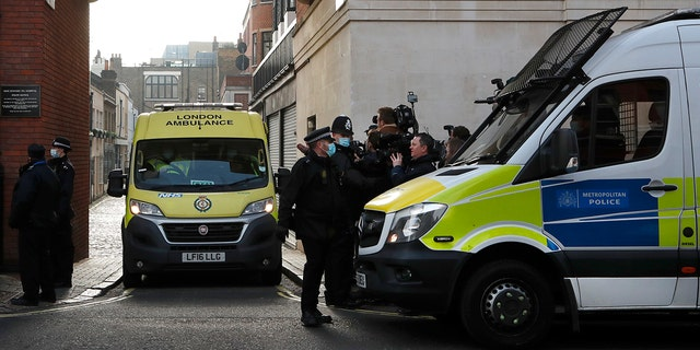 Police officers stand at the entrance to King Edward VII Hospital, where Prince Philip is being treated for an infection, as an ambulance is pulled out, in London, Monday, March 1, 2021.