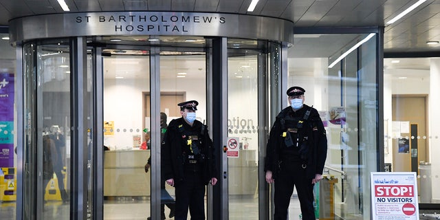 Police officers stand outside the main entrance of St Bartholomew's Hospital where Britain's Prince Philip is being treated in London.