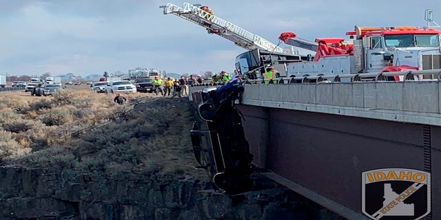 Authorities say a set of camp trailer safety chains and quick, careful work by emergency crews saved two people after their pickup truck plunged off a bridge on March 15, 2021. (Idaho State Police via AP)