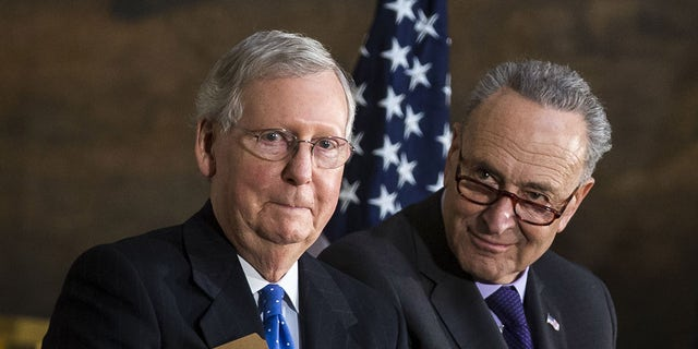 Senate Majority Leader Mitch McConnell, a Republican from Kentucky, from left, Senate Minority Leader Chuck Schumer, a Democrat from New York, applaud during a Congressional Gold Medal ceremony for former Senate Majority Leader Bob Dole, not pictured, at the U.S. Capitol in Washington D.C., on Wednesday, Jan. 17, 2018. Schumer and McConnell both appeared at a committee hearing on Wednesday on S.1, something that Senate leaders rarely do. (Al Drago/Bloomberg via Getty Images)