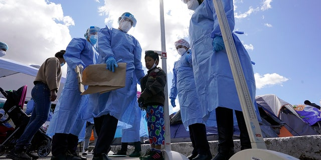 Baja California public health workers measured the height of a boy in a makeshift camp for asylum seekers in the United States at the border crossing on Friday, March 12, 2021, in Tijuana, Mexico.  (AP Photo / Gregory Bull)