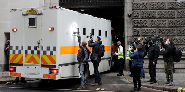 Journalists try to take pictures of the inside of a prison van moving into the Old Bailey on Tuesday. (AP)