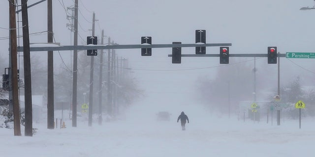 A person trudges across Ridge Road in east Cheyenne, Wyo., on Sunday. (AP/Wyoming Tribune Eagle)