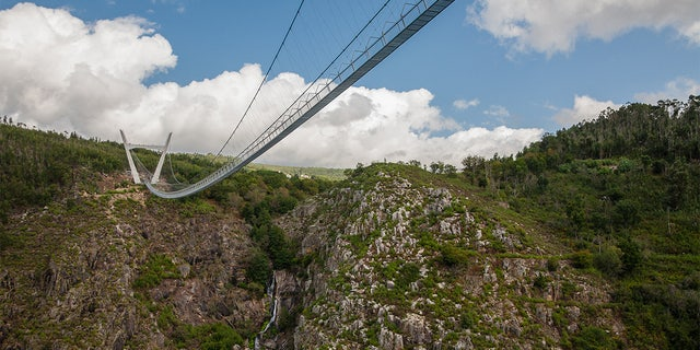 The bridge traverses the fast moving River Paiva in the Arouca Geopark, suspended 574 feet above the water.