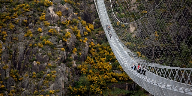 People walk on the world's longest pedestrian suspension bridge '516 Arouca', now open for local residents in Arouca, Portugal.