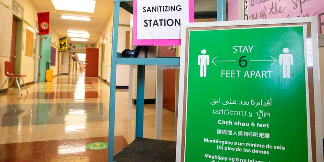A sanitizing station and sign encouraging social distancing sits in the main hallway during the first day of partial in-person instruction at an elementary school in California.