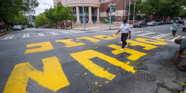 "FILE - In this Wednesday, June 10, 2020, file photo, a man walk across a ""Defund Police"" written in front of the Atlanta Police Department Headquarters. (Alyssa Pointer/Atlanta Journal-Constitution via AP)"