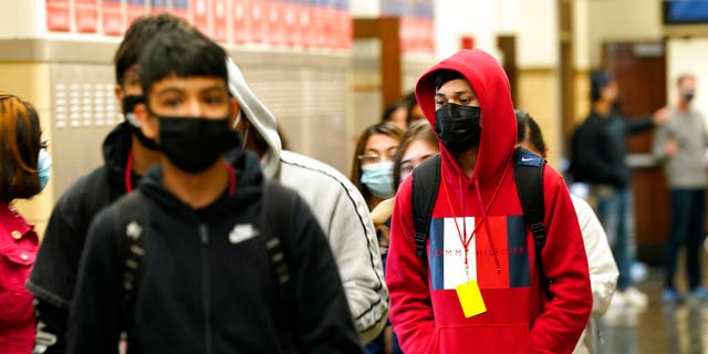 FILE: Students at Wyandotte County High School wear masks as the walk through a hallway on the first day of in-person learning at the school in Kansas City, Kan.