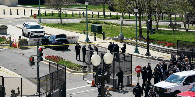 U.S. Capitol Police officers investigate near a car that crashed into a barrier on Capitol Hill near the Senate side of the U.S. Capitol in Washington, Friday, April 2, 2021. (AP Photo/J. Scott Applewhite)