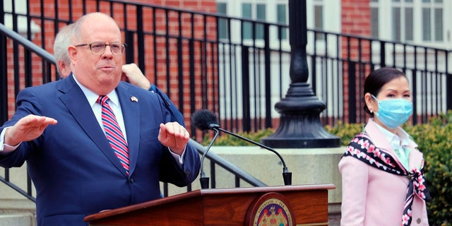 In this April 20, 2020 file photo, Maryland Gov. Larry Hogan speaks at a news conference in Annapolis, Md., with his wife, Yumi Hogan, right, On Friday, Hogan vetoed three proposals packaged with police reform legislation. (AP Photo/Brian Witte, File)