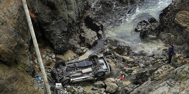 In the Bodega Head parking lot in Bodega Bay, California, a car fell from a wooden fence to the left and landed on a 100-foot-high rocky coastline, killing two people. Bodega Bay firefighters tried to secure the SUV at the crash site. Saturday, April 3, 2021 (Kent Porter/News Democrats through AP)