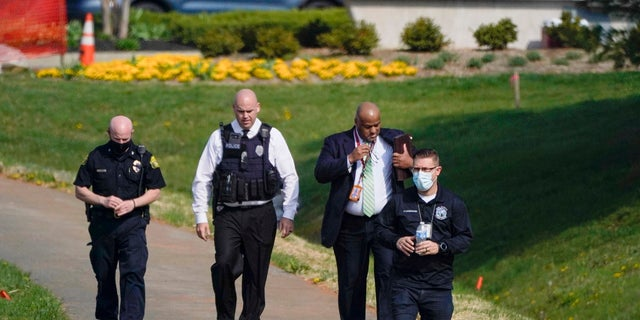 Police walk near the scene of a shooting at a business park in Frederick, Md., Tuesday, April 6, 2021. (AP Photo/Julio Cortez)