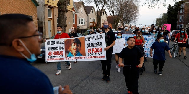 Members of Chicago's Little Village Community Council march on Tuesday, April 6, 2021 to protest against the death of 13-year-old Adam Toledo, who was shot by a Chicago Police officer at about 2 a.m. on March 29 in an alley west of the 2300 block of South Sawyer Avenue near Farragut Career Academy High School. (AP Photo/Shafkat Anowar)