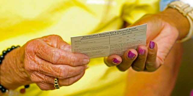 April 7, 2021: Linda Busby, 74, receives a vaccination card after receiving a shot of the Johnson & Johnson COVID-19 vaccine at the Aaron E. Henry Community Health Service Center in Clarksdale, Miss.