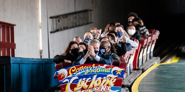 New York City Mayor Bill de Blasio finishes a ride on the Cyclone rollercoaster after attending the ribbon cutting and seasonal opening of the Coney Island amusement park area, Friday, April 9, 2021, in the Brooklyn borough of New York. Coney Island's illustrious amusement parks are reopening Friday after the coronavirus pandemic shuttered them all last year. AP Photo/John Minchillo)